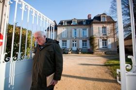 Жан Ванье у ворот своего дома в Троли. Троли - это не специализированное поселение, а обычная деревня на севере Франции. В ней живут 2200 жителей. 10% из них - умственно отсталые, 7% - те, кто им помогает, а остальные 83% - самые обычные люди.